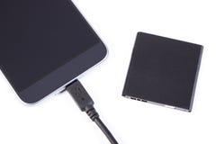 Handy, Stecker des Ladegeräts und Telefonbatterie, Smartphoneaufladung Lizenzfreie Stockfotos