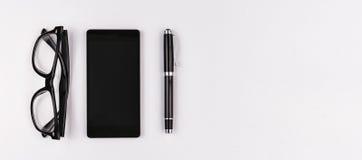 Handy, Stift und Brillen auf weißem Hintergrund Lizenzfreies Stockbild