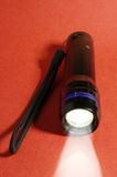 Handy torch with a light beam Stock Photography