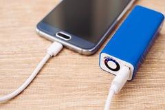 Handy- und Batterieleistung haben Ladegerät auf einem Schreibtisch ein Bankkonto Lizenzfreie Stockfotos