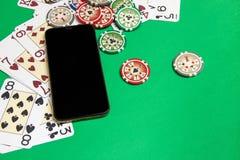 Handy und Pokerchips mit Spielkarten auf einer grünen Tabelle Spielautomat innerhalb des Tablet-PCs auf einem wei?en Hintergrund stockbild