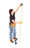 A handy woman measuring for work. Stock Image
