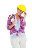 Handy woman touching her helmet and holding paintbrush Stock Photo