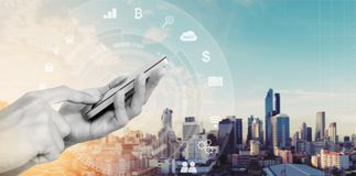 Handyanwendung und -technologie Hand unter Verwendung des beweglichen intelligenten Telefon- und Stadtsonnenaufganghintergrundes lizenzfreies stockbild