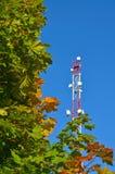 Handykommunikationsradio-Fernsehturm, Mast, Zellmikrowellenantennen und Übermittler gegen den blauen Himmel und die Bäume Lizenzfreies Stockbild
