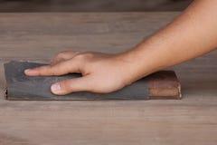 Handyman που λειτουργεί με το γυαλόχαρτο σε έναν ξύλινο πίνακα Στοκ εικόνα με δικαίωμα ελεύθερης χρήσης