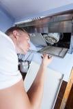Handyman που επισκευάζει τον ανεμιστήρα εξολκέων κουζινών Στοκ εικόνα με δικαίωμα ελεύθερης χρήσης