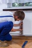 Handyman που επισκευάζει το θερμαντικό σώμα στοκ φωτογραφίες