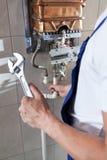 Handyman που επισκευάζει το θερμοσίφωνα αερίου Στοκ φωτογραφία με δικαίωμα ελεύθερης χρήσης