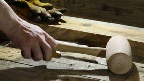 Handyman που καταγράφει τα εργαλεία ξυλουργικής στις ξύλινες σανίδες στο εργαστήριο ξυλουργών απόθεμα βίντεο