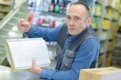 Handyman που παρουσιάζει έγγραφο στην αποθήκη εμπορευμάτων Στοκ εικόνες με δικαίωμα ελεύθερης χρήσης