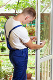 Handyman που ρυθμίζει μια λαβή παραθύρων στοκ εικόνα με δικαίωμα ελεύθερης χρήσης