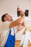 Handyman χρησιμοποιώντας ένα ασύρματο τρυπάνι στο ανώτατο όριο στοκ εικόνα