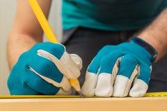 Handyman χρησιμοποιώντας μολύβι ξυλουργών για να χαρακτηρίσει τη σανίδα Στοκ Φωτογραφίες