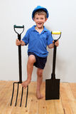 Handyman. Boy with hard-hat on holding a fork and shovel stock photo