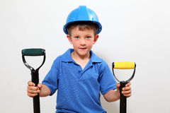 Handyman. Boy with hard-hat on holding a fork and shovel stock photography