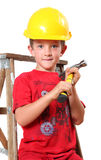 Handyman. Boy sitting on a ladder with a hammer in hand and hard hat on his head royalty free stock photos