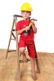 Handyman. Boy sitting on a ladder with a hammer in hand and hard hat on his head stock photography