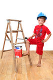 Handyman. Boy with hard hat on, standing at a wooden ladder with paintbrush and paint royalty free stock photo