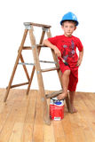 Handyman. Boy with hard hat on, standing at a wooden ladder with paintbrush and paint royalty free stock photos
