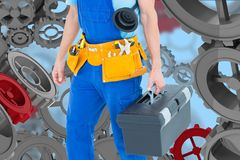 Handyman against background with 3D cogs. Digital composite of handyman  gainst back with 3d cogs Royalty Free Stock Photography