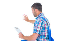 Handyman analyzing while holding clipboard Royalty Free Stock Images