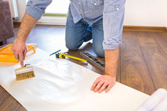 Handyman applying blue for a wallpaper Stock Images