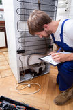 Handyman bends down, looks at the fridge Royalty Free Stock Images