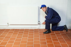Handyman in blue boiler suit repairing a radiator smiling at camera Stock Photography