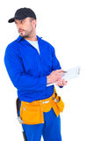 Handyman in blue overall writing on clipboard Stock Photos