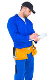 Handyman in blue overall writing on clipboard Stock Photo