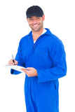 Handyman in blue overall writing on clipboard Stock Images