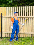 Handyman in blue overalls dreaming on the rest Stock Photo