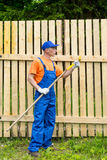 Handyman in blue working uniform checks the condition of paint roller Stock Images