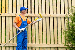 Handyman in blue working uniform checks the condition of paint roller Royalty Free Stock Photography