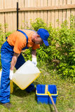 Handyman in blue working uniform pours yellow antiseptic paint from can. To bucket Royalty Free Stock Image