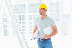 Handyman with blueprints and clipboard in office Stock Photos