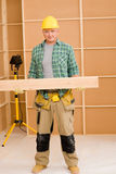 Handyman carpenter mature carry wooden beam Royalty Free Stock Photo
