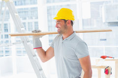 Handyman carrying planks in building Stock Images