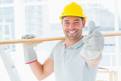 Handyman carrying wood while gesturing thumbs up Royalty Free Stock Photos