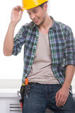 Handyman. Cheerful craftsperson adjusting his hardhat and smiling stock photography