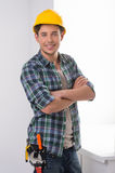 Handyman. Cheerful craftsperson looking at camera and keeping arms crossed royalty free stock images