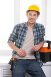 Handyman. Cheerful craftsperson looking at camera and leaning at the windowsill royalty free stock image