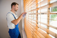 Handyman cleaning blinds with a towel Royalty Free Stock Photo