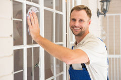 Handyman cleaning the window and smiling Royalty Free Stock Photo
