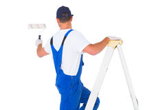 Handyman climbing ladder while using paint roller Royalty Free Stock Image