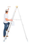 Handyman climbing ladder while using paint roller Stock Photography