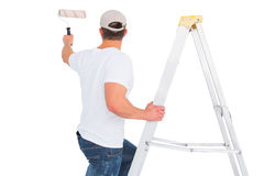 Handyman climbing ladder while using paint roller Stock Photos