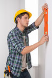 Handyman. Confident craftsperson in hardhat measuring the wall level royalty free stock photography