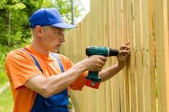 Handyman constructing the wooden fence. Using cordless screwdriver stock photos
